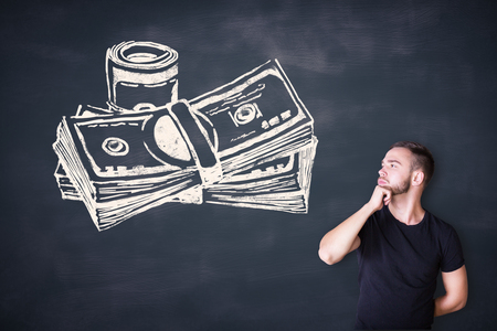thoughtful: Thoughtful casual young man looking at cash sketh on blackboard background