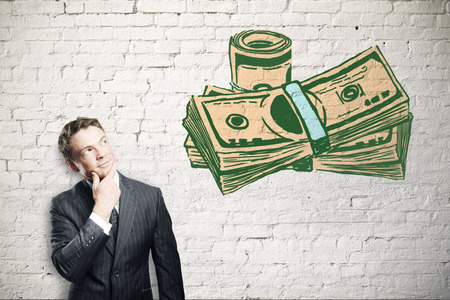 thoughtful: Thoughtful young man looking at creative dollar banknote drawing on white brick background. Financial growth concept