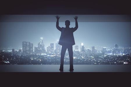 under pressure: Struggling man between concrete walls on illuminated night city background. Pressure concept