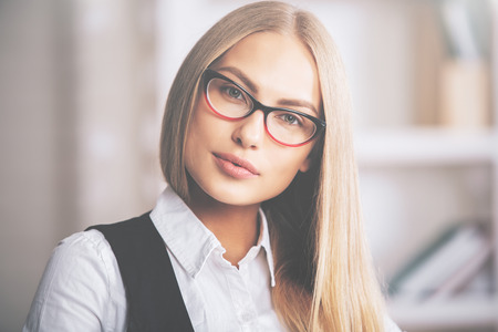Office women: Portrait of focused young female in formal outfit and eyeglasses