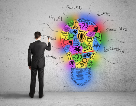 idea bulb: Back view of young businessman drawing colorful light bulb on textured concrete wall. Creative idea concept