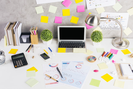 financial reports: Close up of creative workplace with blank laptop, smartphone, colorful stickers, decorative plants, financial reports and other items. Mock up Stock Photo
