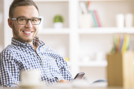 Closeup portrait of young european businessman in casual shirt and glasses using smartphone at workplace