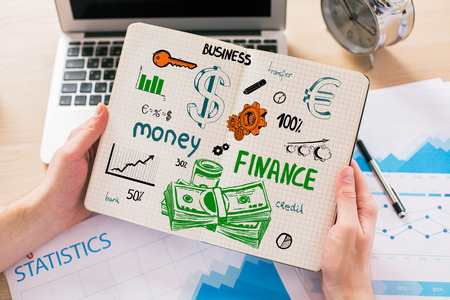 finance report: Close up of male hands holding notepad with creative finance sketch above workplace with laptop, business report and other items. Financial growth concept