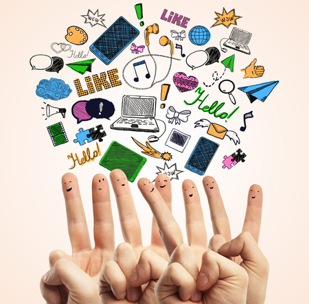 creative communication: Creative image of hands with smiley faces on fingers showing peace signs on light background with colorful communication icons. Social media concept Stock Photo
