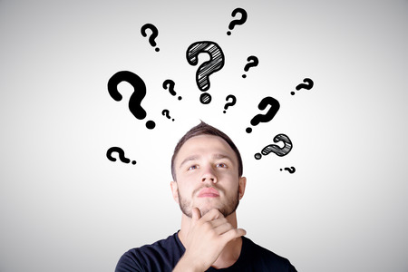 thoughtful: Portrait of handsome thoughtful man with question mark sketches Stock Photo