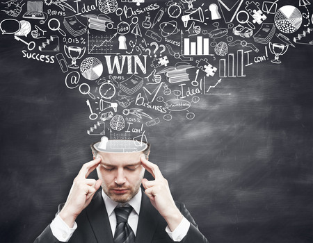 brain storming: Pensive young businessman with business sketch coming out of his head on blackboard background. Brainstorming concept