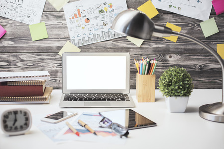 decorative objects: Front view and close up of creative designer desktop with blank white laptop, other gadgets, sketchings, decorative items and other objects. Mock up Stock Photo