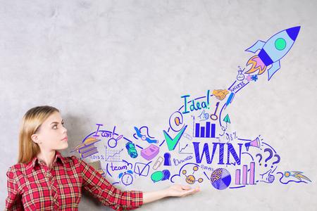 european: Attractive european girl presenting creative rocket ship sketch drawn on concrete wall. Start up concept