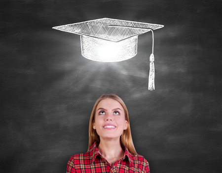 mortarboard: Pretty caucasian female in casual shirt looking up on chalkboard background with creative mortarboard sketch. Graduation concept