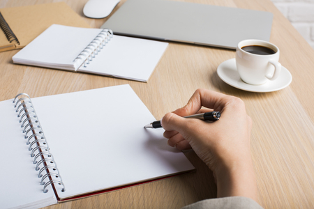 Side view of womans hand writing in blank spiral notepad placed on wooden desktop with pencils, closed laptop and coffee cup. Mock up
