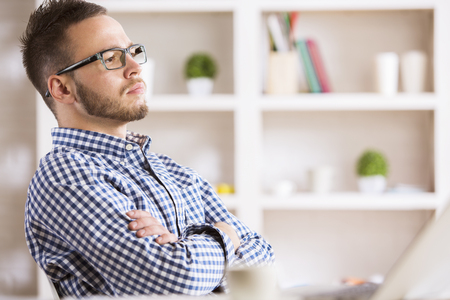 Portrait of thoughtful young man in casual shirt and glasses at workplace