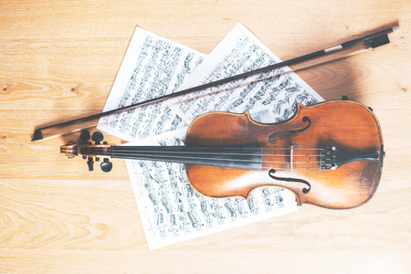 Violin, bow and music sheets placed horizontally on light wooden floor. Concert rehearsal concept