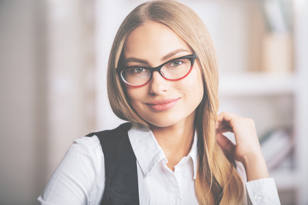 Portrait of beatiful young businesslady with hand in blonde hair, wearing formal outfit and glasses Stock Photo