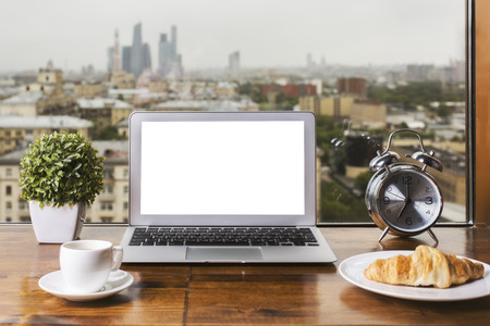 Wooden windowsill with blank white laptop, coffee cup, croissant on plate, decorative plant and silver alarm clock on city view background. Mock up