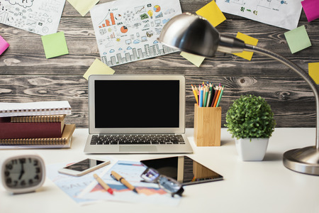 decorative objects: Front view and close up of creative designer desktop with blank laptop, other devices, sketchings, decorative items and other objects. Mock up