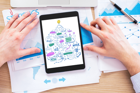 financial reports: Closeup of businessman hands using tablet with business sketch on screen above workplace with printed financial reports Stock Photo