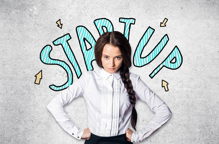 Portrait of determined caucasian girl on concrete background with start up sketch. Startup concept Stock Photo