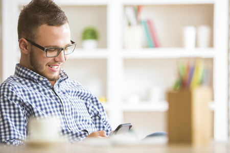 businessman phone: Closeup portrait of young european businessman in casual shirt and glasses using cellphone at workplace