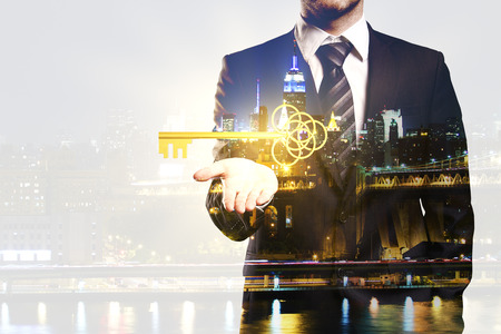 business security: Businessman holding ornate golden key on night city background with copy space. Double exposure