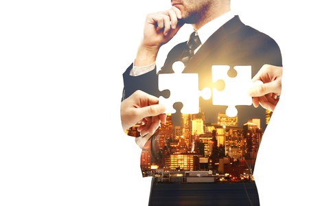 copyspace: Thoughtful businessman on city background with puzzle pieces and copy space. Double exposure. Partnership and teamwork concept Stock Photo