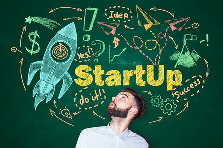 man looking up: Surprised young man looking up at creative startup sketch on chalkboard background. Start up concept