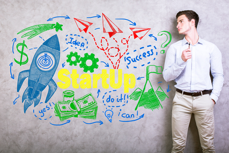 Handsome young man standing against concrete wall with creative colorful rocket ship drawing. Start up concept Stock Photo