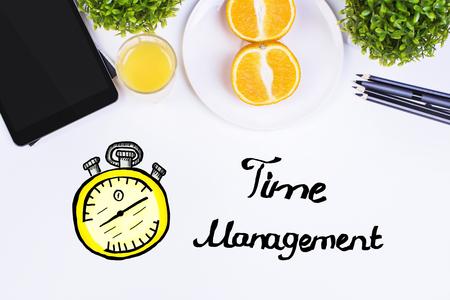 puntualidad: Vista desde arriba de la mesa blanca con dispositivos electrónicos, plantas decorativas, mitades de naranja, suministros y creativa boceto reloj. el concepto de gestión