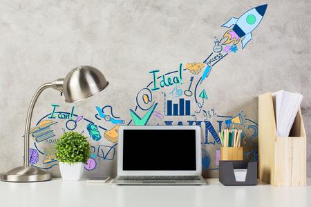 Vista frontale del posto di lavoro con creativi razzo schizzo, schermo bianco del computer portatile, forniture, impianti e altri oggetti. Mock up, Start up concept