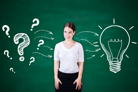 Attractive young woman on chalkboard background with creative light bulb and question marks sketch. Idea concept