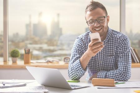 Portret van de knappe Europese mens die cellphone gebruiken terwijl het zitten bij bureaulijst met laptop computer en andere punten