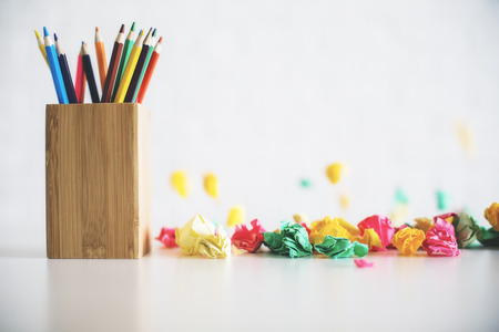 pencil holder: Close up of wooden pencil holder and colorful crumpled paper balls on bright tabletop