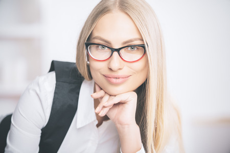Portrait of gorgeous smiling caucasian businesswoman in eyeglasses and formal outfit
