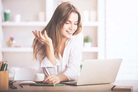 Portret van schitterende, glimlachende jonge vrouwelijke gebruikende laptop computer op het werk