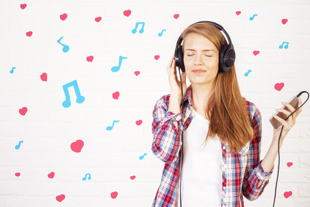 cellular: Joyful young woman with smartphone and headphones on light background with musical notes and hearts. Music lover concept Stock Photo