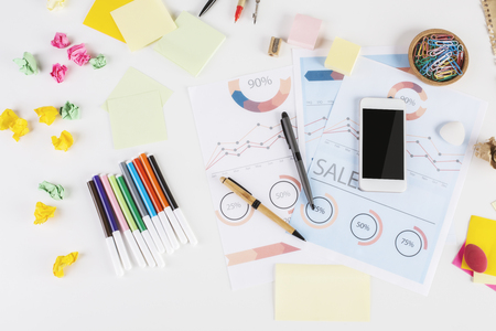business supplies: Top view of messy office desktop with colorful supplies, business report and blank smartphone. Mock up Stock Photo
