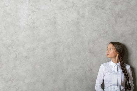 Portrait d'une belle femme européenne sur fond de mur en béton texturé avec copie