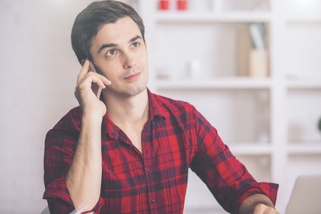 young guy: Portrait of attractive young guy in casual red shirt talking on cellular phone