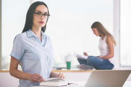 daylight: Two beautiful young girls reading in modern bright office with daylight Stock Photo