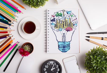 business supplies: Top view of white desktop with creative colorful business sketch inside light bulb and supplies. Idea concept