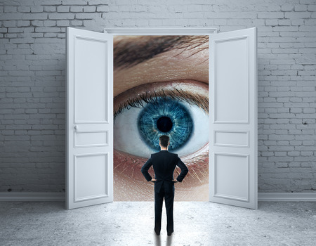 Back view of businessman in brick interior with open door and abstract blue eye. Vision concept