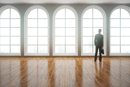 shiny floor: Back view of young businessman in suit looking out of window in modern interior with clean shiny wooden floor. 3D Rendering Stock Photo