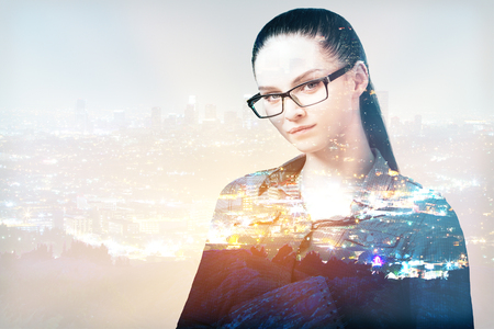 Attractive young businesswoman in glasses on abstract city background with copy space. Double exposure