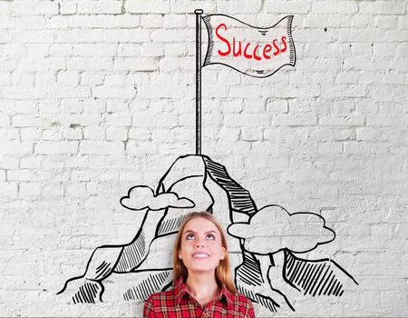 Sourire jeune femme sur fond de briques avec création sommet de la montagne croquis. concept de réussite et de leadership