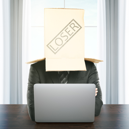 masquerader: Cardboard box with loser stamp on the head of a businessman using laptop at workplace. Failure concept. 3D Rendering