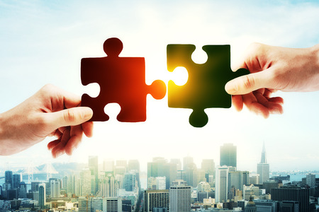 holding close: Hands putting puzzle piece together on bright city background with sunlight. Teamwork concept