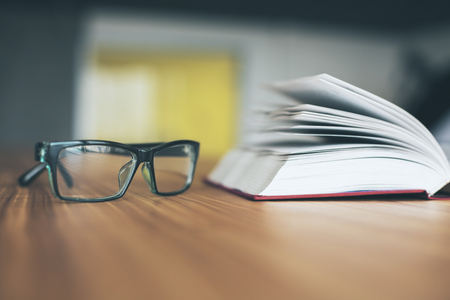 Closeup of glasses and open book on wooden desktop.