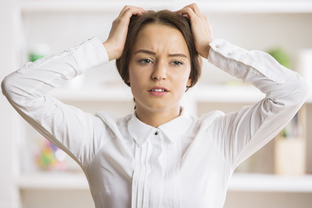 Portrait of worried young woman at workplace Stock Photo