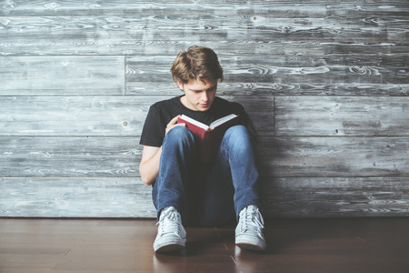 young guy: Handsome young guy sitting on wooden floor and reading book. Education and leisure reading concept Stock Photo