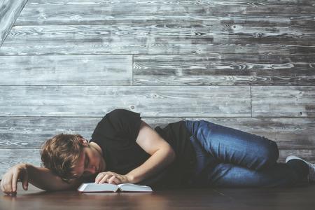 Zufälliger junger Mann mit dem offenen Buch, das auf Bretterboden schläft. Müde und überarbeitete Konzept